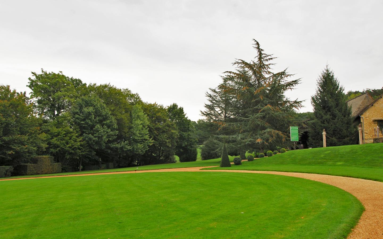 widok na obły trawnik w parku zabytkowym